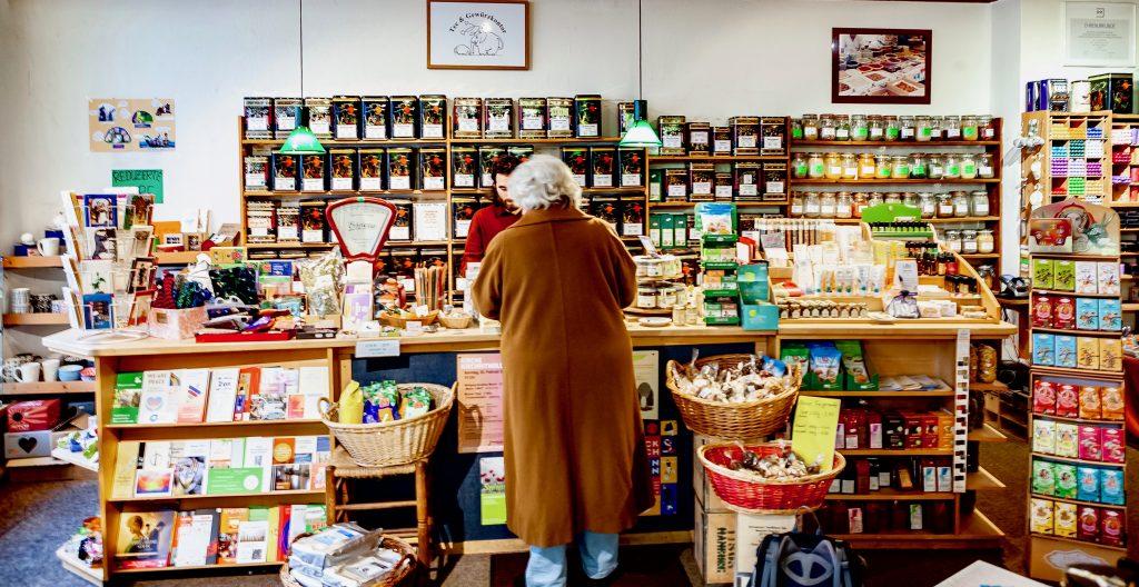Teeladen innen, Frontalansicht, im Hintergrund Tee- und Gewürzdosen, im Vordergrund ein Angestellter an der Theke, der einen Kunden bedient.